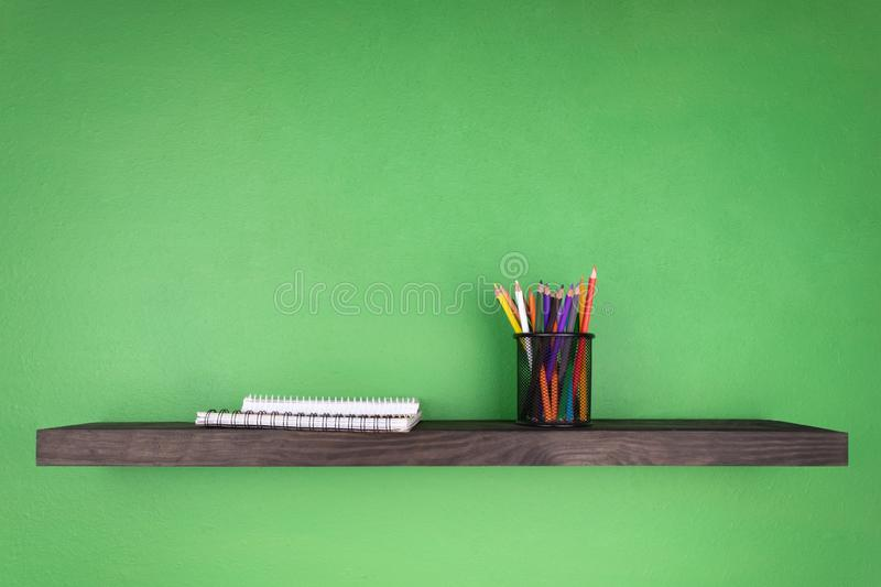 A dark wooden shelf against the background of a green wall on which is set a glass with pencils and notebooks with binding stock photography