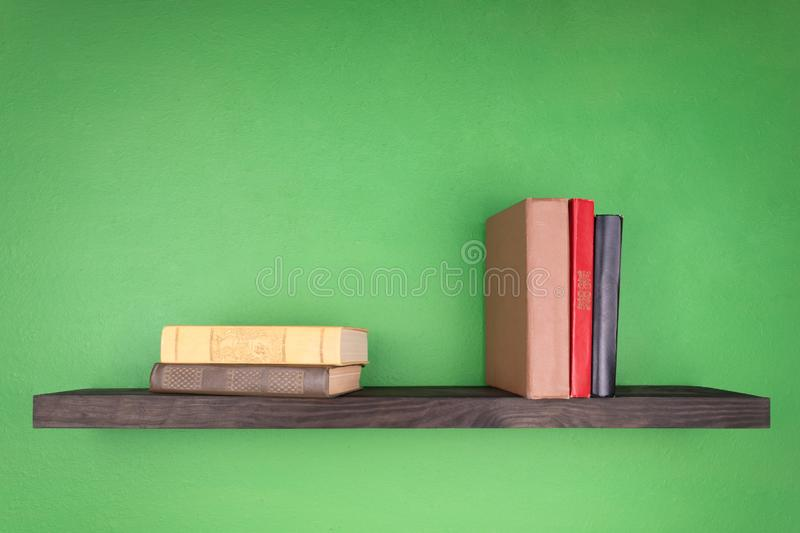 A dark wooden shelf on the green wall, two books are on it and three books are standing vertically royalty free stock images