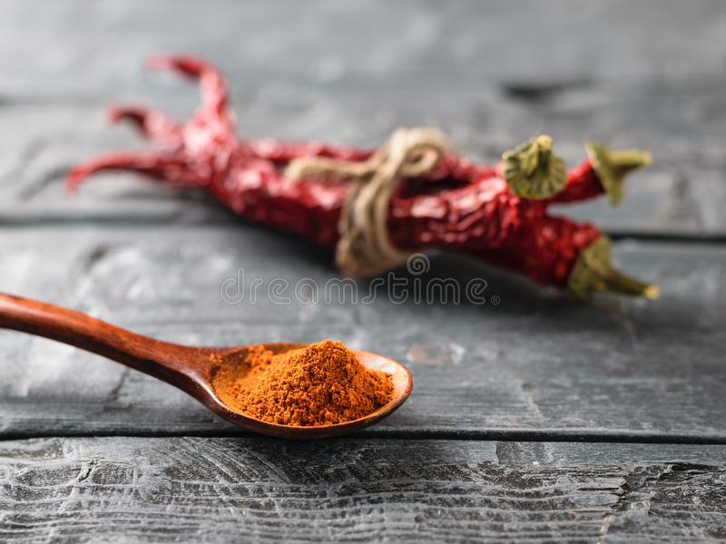 A dark wooden spoon with ground pepper and a bunch of chili pods on the rustic table. Universal seasoning for all dishes royalty free stock photos