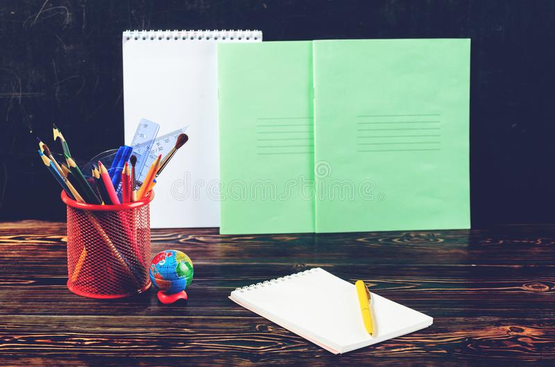 Dark wooden table with pencil holder, colorful pencils, notebook stock image