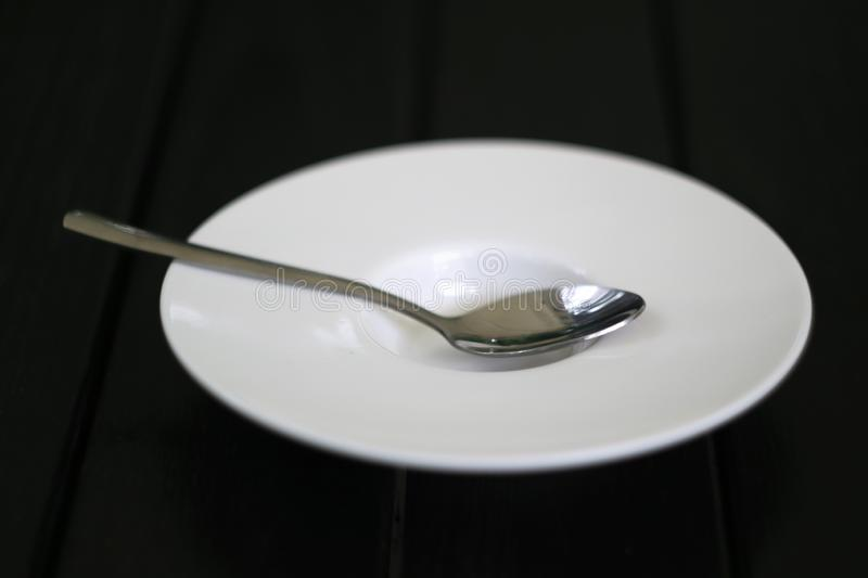On a dark wooden table is a plate and a spoon inside a close distance stock image