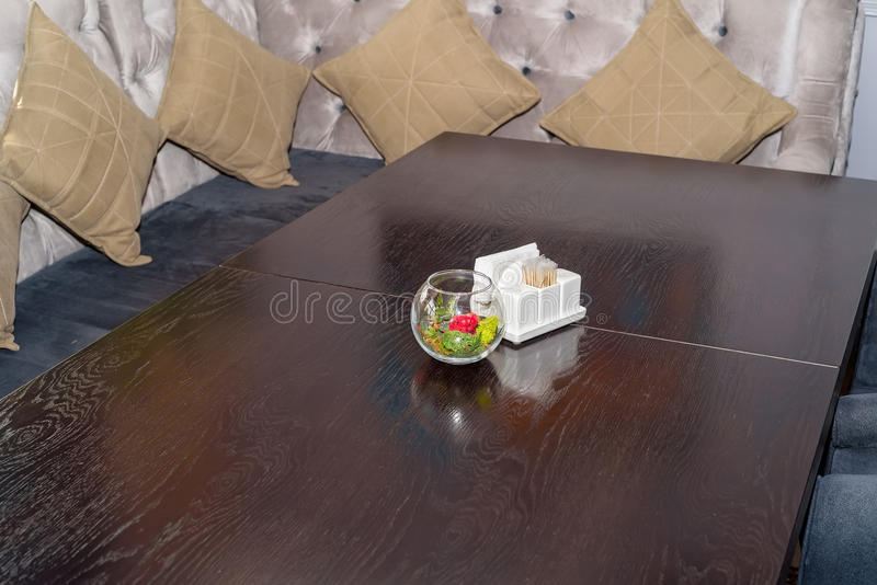 cafe interior wooden table with salt pepper in flower decoration with comfortable sofa and cushions in background
