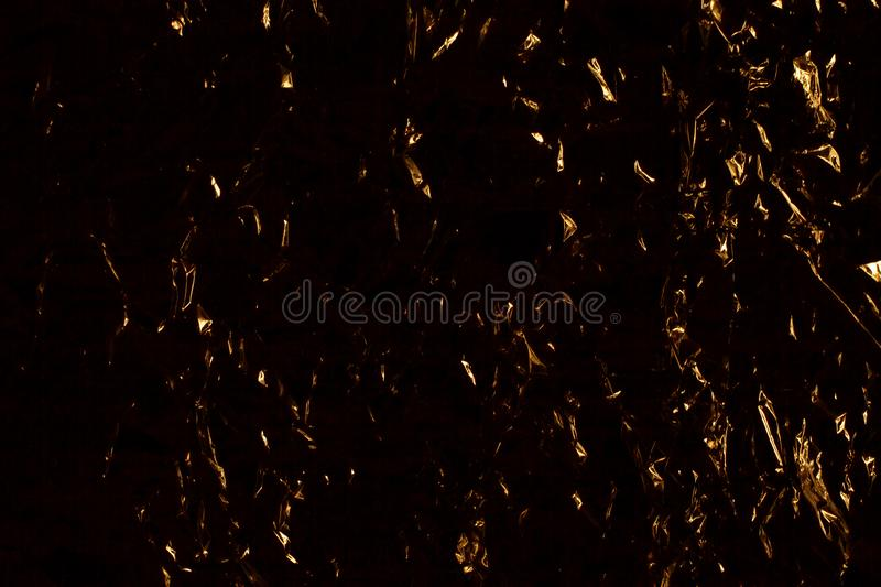 Dark yellow and black abstract background, golden shining metallic surface, crumpled gold metal shiny backdrop design. Sharp hard gloom texture pattern, golden stock images