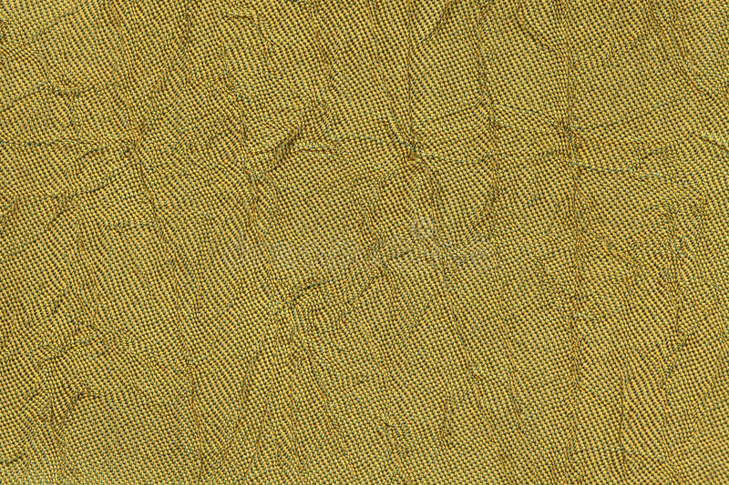 Dark yellow wavy background from a textile material. Fabric with fold texture closeup. Creased shiny golden cloth royalty free stock image