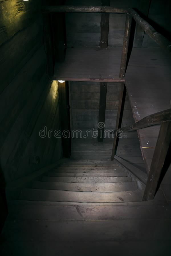Darkness and horror in a ghostly building. Inside on a dark wooden staircase with steps down to the basement of an old abandoned stock images