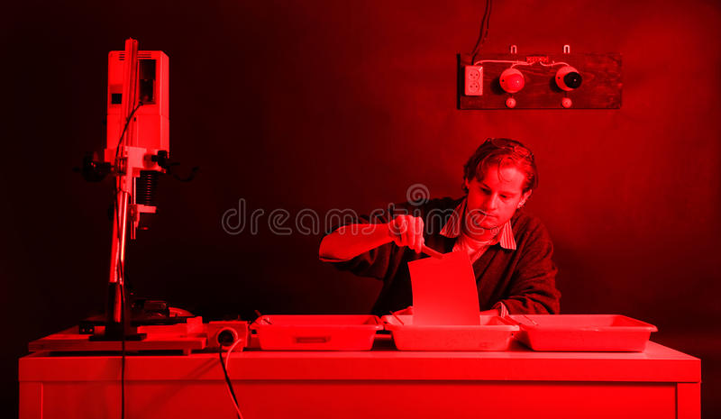 Darkroom laborant. Dedicated and diligent photographer, removing a freshly printed photo from the stop bath in a darkroom stock images