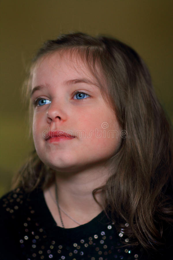 Darling Little Girl Looking Off. A closeup of a sweet young little brunette tween girl with blue eyes looking off in the distance. Shallow depth of field stock photo