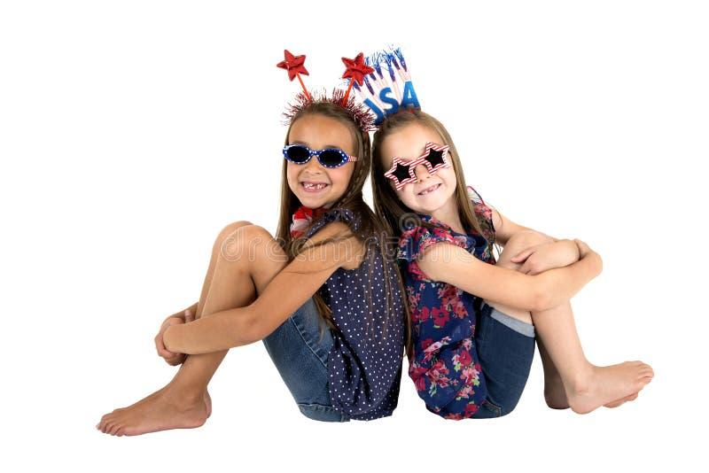 Darling USA patriotic girls sitting missing front teeth smiling. Patriotic girls sitting missing front teeth smiling stock images