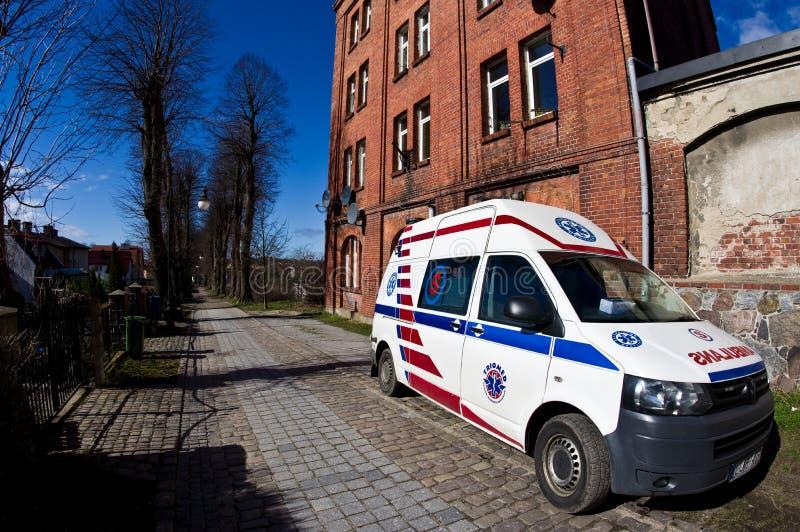 Darlowo, Polen - noodsituatieziekenwagen die bij baksteenhuis met meerdere gezinnen wordt geparkeerd stock foto's