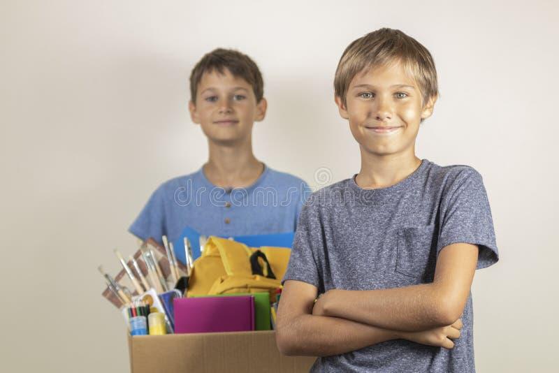Darowizny poj?cie Żartuje szczęśliwego pomagać inny Chłopiec z darowizną boksują z książkami i szkolnymi dostawami fotografia royalty free