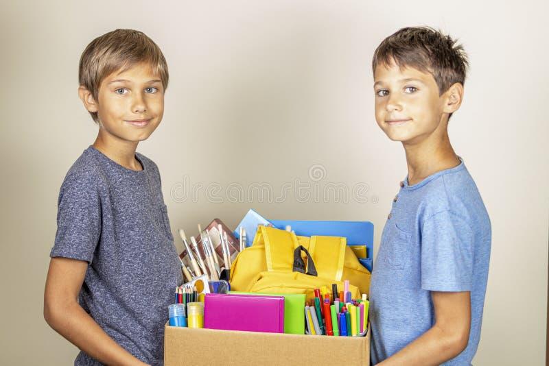 Darowizny poj?cie Dzieciaków trzymać daruje pudełko z książkami i szkolnymi dostawami obrazy royalty free
