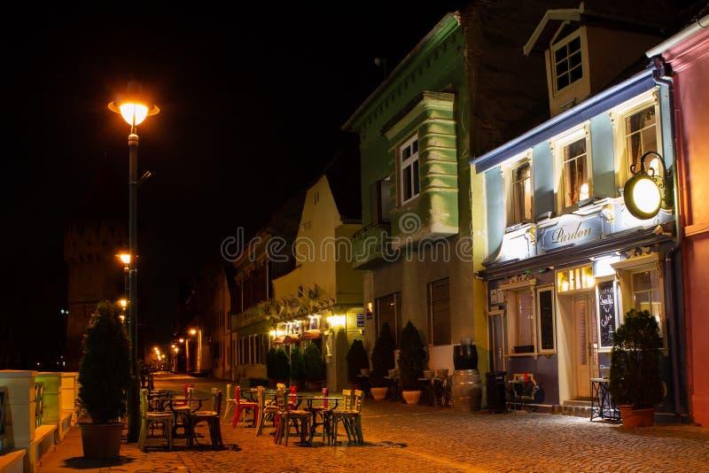 Darowuje kawiarni na Cetatii Ulicznym strada Cetatii w Sibiu, przy nocą, z pustymi stołami i krzesłami zdjęcie stock