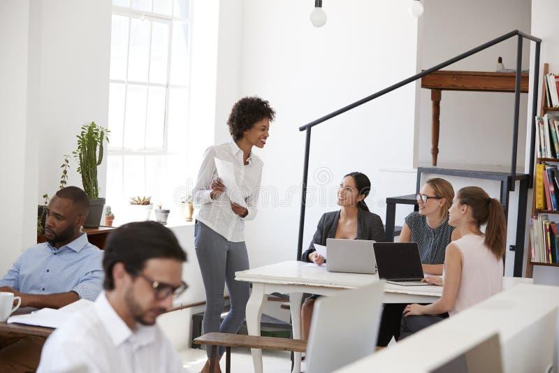 Darstellende Dokumente der Frau zu den Kollegen an einem Schreibtisch im Büro stockfotos