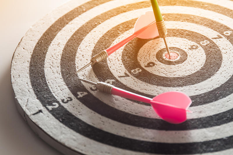 Dart arrow hitting in the target center of dartboard stock images