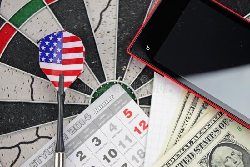 Dart arrow, phone, dollars and pad stock photos