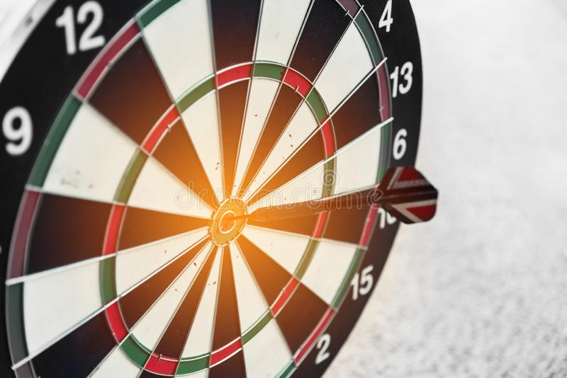 Dart board and arrow in middle. Business and success concept. Achievement and target theme. Orange sun light effect. High contrast. Tone, outdoors, 100 royalty free stock photo