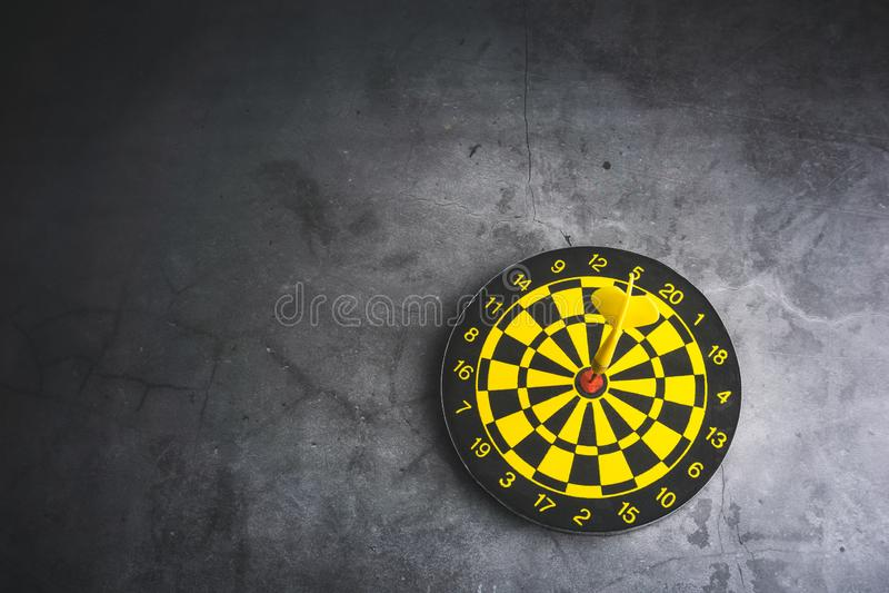 Dart board with yellow arrows hitting target, closeup stock image