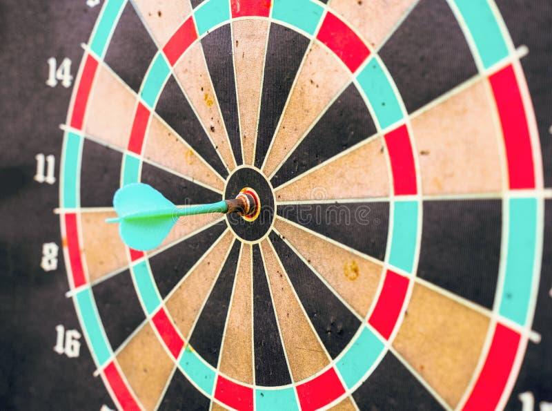 Dart in bullseye center of target on aged dartboard royalty free stock image