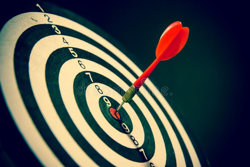 Dart hits center Bullseye is a target and goal of business, vintage style stock images