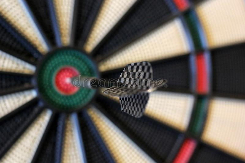 Dart hits target in the centre of dartboard stock photography