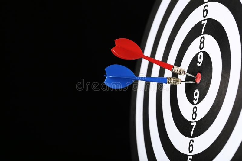 Dartboard with darts. On black background royalty free stock images