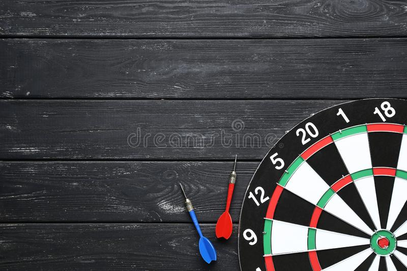 Dartboard with darts. On black wooden table stock photo