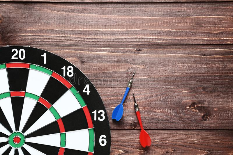 Dartboard with darts. On brown wooden table royalty free stock image