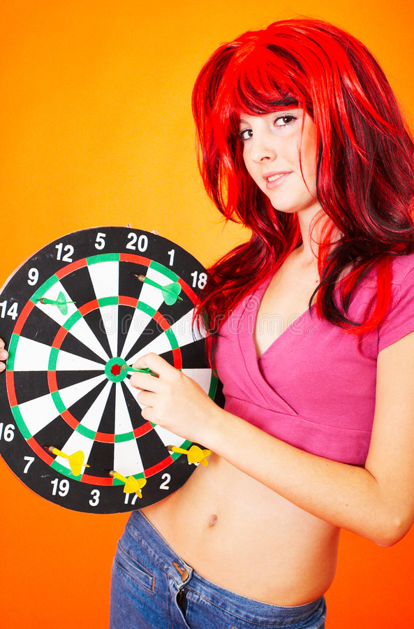 Dartboard Girl. Teenage girl in red wig holding a dartboard, other hand on dart in bullseye royalty free stock image