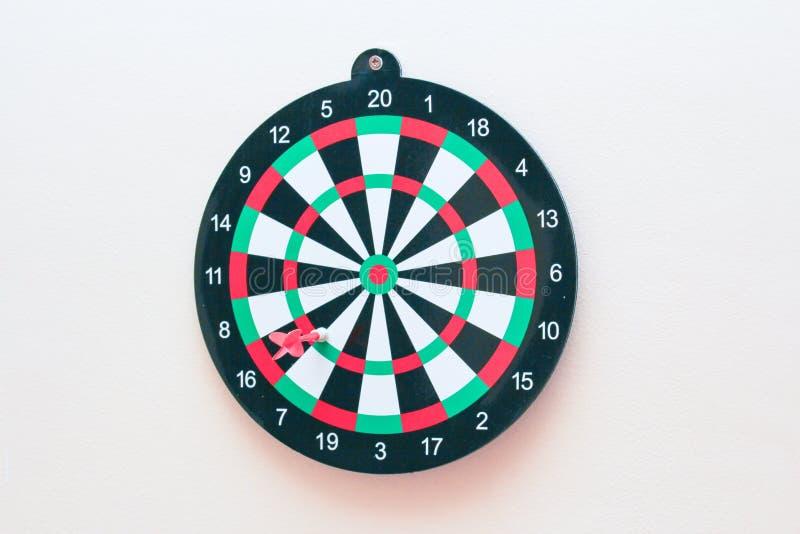 Dartboard met een pijltje op grijze muur dichte omhooggaand stock foto's