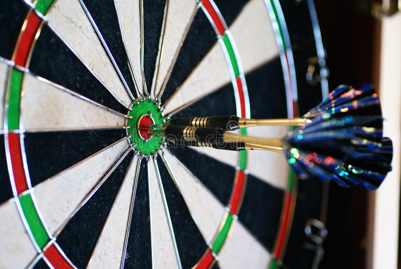 Darts. Three darts in the bull-eye of target stock photo