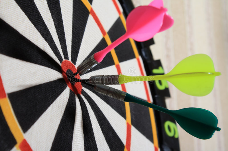 Darts. Three darts of different color in the center of a target stock photos