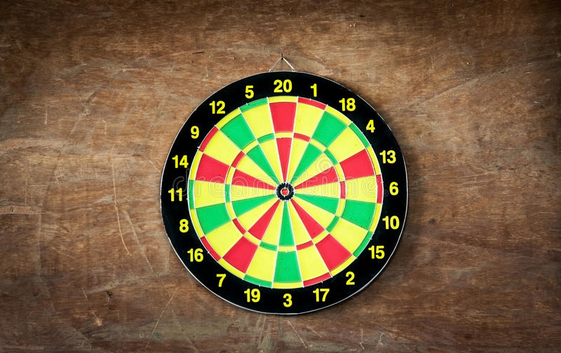 Darts board on wood background. Green yellow red dartboard hanking on wood wall royalty free stock image