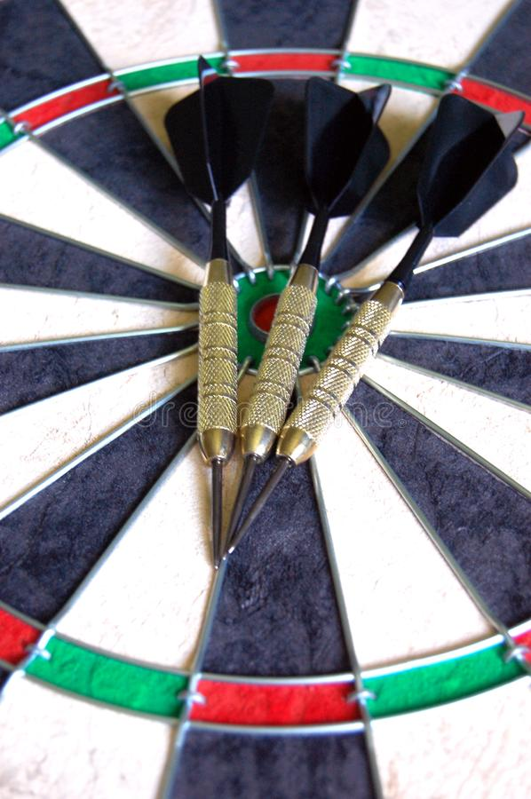 Darts on a Dartboard. Three black and gold darts laying on a new dartboard royalty free stock photo