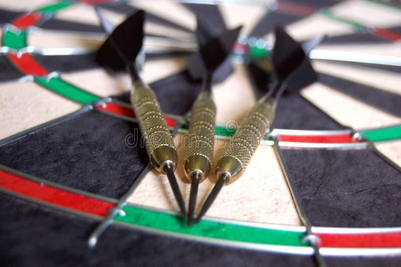 Darts on a Dartboard. Three black and gold darts laying on a new dartboard stock photo