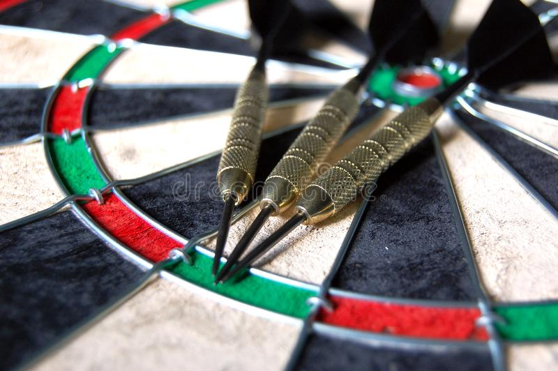 Darts on a Dartboard. Three black and gold darts laying on a new dartboard stock images