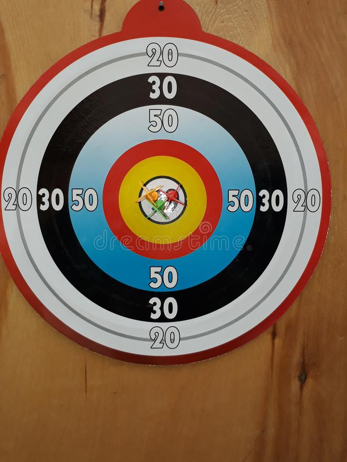 Of Darts game is to hit a round bright digits on a wooden door. Sports game of Darts accuracy training royalty free stock photos