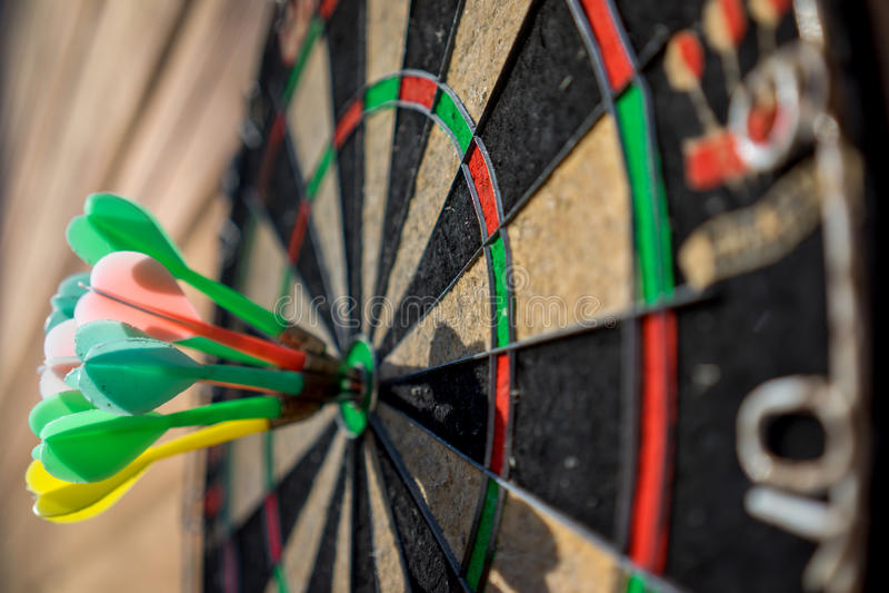 Darts. Hitting bullseye on dartboard royalty free stock image