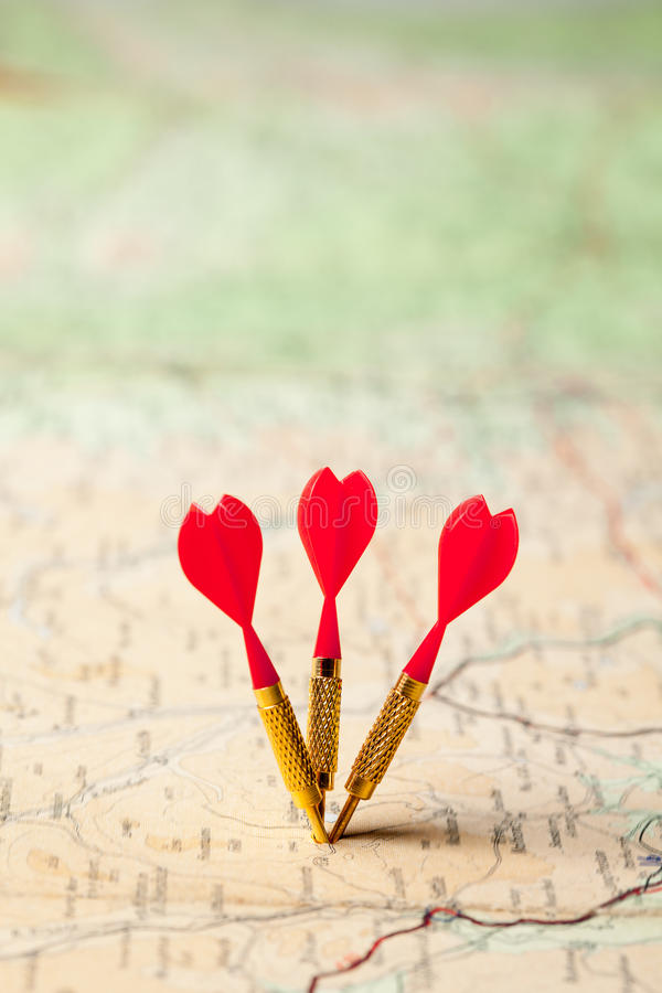 Darts in a map. Three red darts in a shallow focus map stock photography