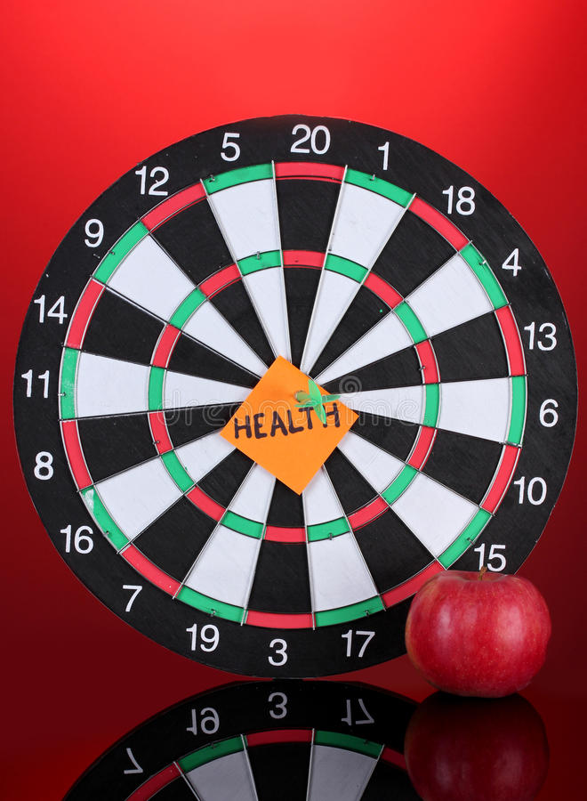 Darts with a sticker symbolizing health. On colorful background royalty free stock images