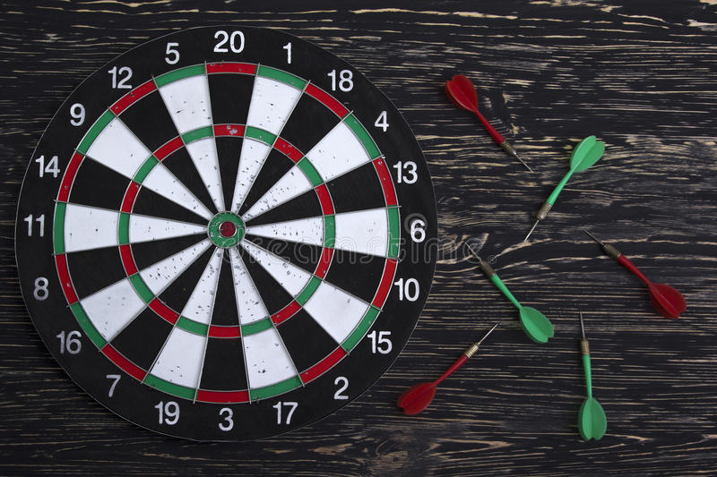 The darts on wooden background. The darts on dark wooden background royalty free stock photos