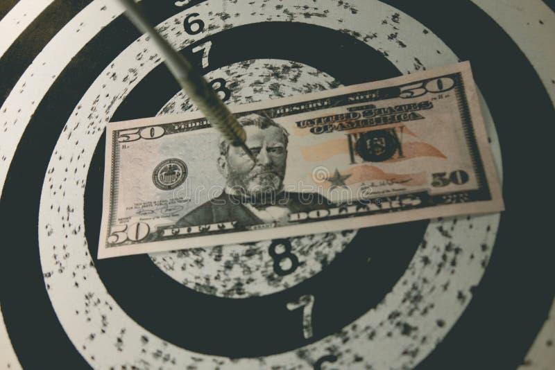 Dartscheibe mit Pfeilen auf Ziel mit Ihrem Geld stockbild