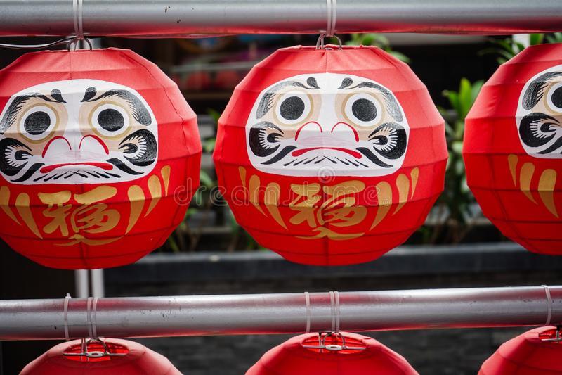 """Daruma dolls. The Japanese lucky symbolic dolls hanging in the row with text translation """"fortune. The Daruma dolls. The Japanese lucky symbolic dolls royalty free stock images"""