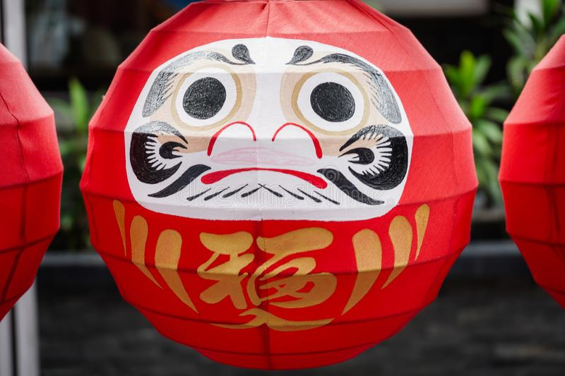"""The Daruma dolls. The Japanese lucky symbolic dolls hanging in the row with text translation """"fortune. Daruma dolls. The Japanese lucky symbolic dolls stock images"""