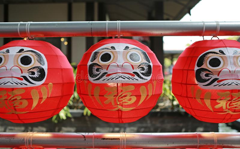 """Daruma dolls. The Japanese lucky symbolic dolls hanging in the row with text translation """"fortune`.  stock photography"""