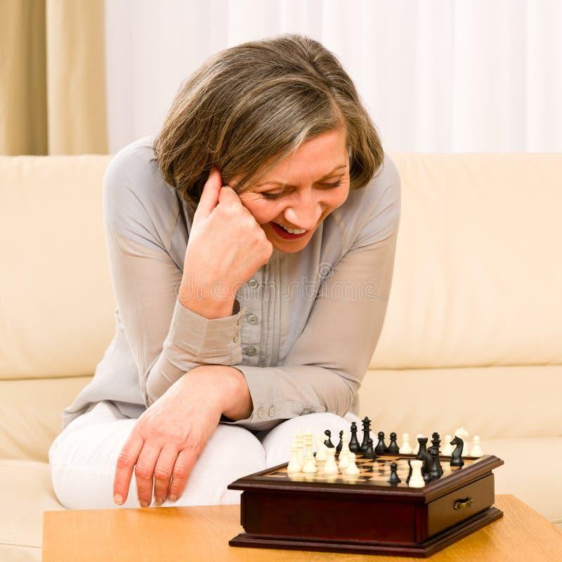 Das ältere glückliche Frauenspielschach sitzen auf Sofa lizenzfreie stockfotos