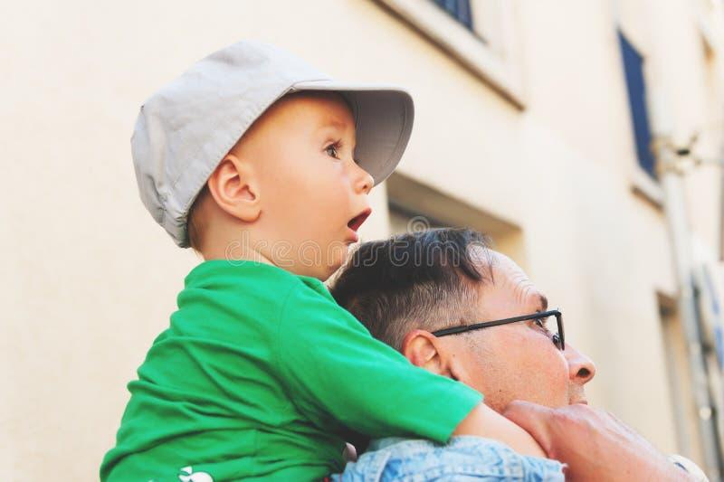 Das überraschte Baby, das auf Vater ` s sitzt, schultert stockfotografie