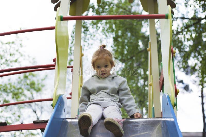 Das überraschte Kind, das hinunter Kinder schaut, schieben stockbild