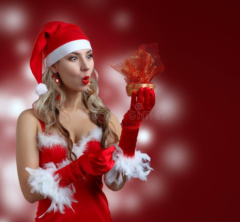 Das überraschte schöne Mädchen, das Weihnachtsmann trägt, kleidet mit Christus lizenzfreies stockfoto