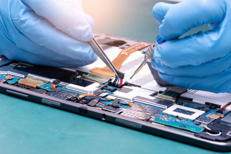 Das abstrakte Bild des asiatischen Technikers, der innerhalb der Tablette durch Schraubenzieher im Labor zusammenbaut stockfotos