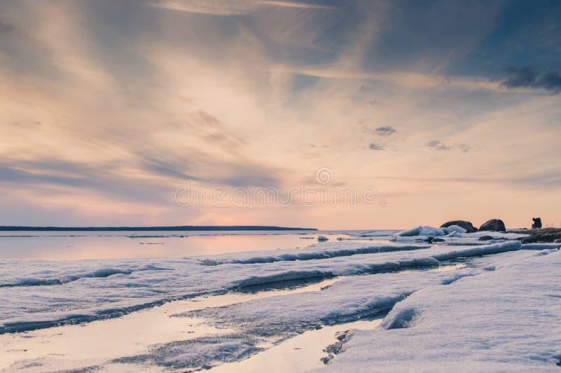Das abstrakte Bild des Sonnenuntergangs am See mit dem schmelzenden Eis im Vorfrühling Goldene Stundenfarben, -gras und -steine S stockbilder
